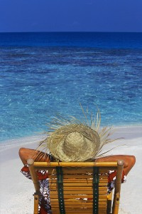 The back view of a man wearing a straw hat while relaxing in a beach chair, facing the Indian Ocean near the coastline in the Maldives. 2000 Maldives